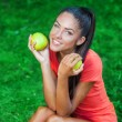 Young beautiful brunette woman holding two apples — Stock Photo