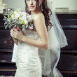 Young beautiful bride holding bouquet of flowers. — Stock Photo #31089971