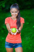 Young beautiful brunette woman holding apple — Stock Photo