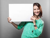 Young brunette woman holding blank sign — Stockfoto