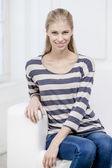 Giovane donna bionda bella sittin sul divano — Foto Stock