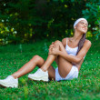 Stock Photo: Injured sportswomsitting on grass