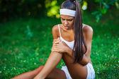 Skadade idrottskvinna sitter på gräset — Stockfoto