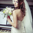 Young beautiful bride holding bouquet of flowers. — Stock Photo #31576615