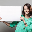 Young brunette woman holding blank sign — Stok fotoğraf