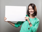 Young brunette woman holding blank sign — ストック写真
