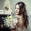 Young beautiful bride holding bouquet of flowers. — Stock Photo #31595177