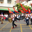 Постер, плакат: Young Men Carry Flags and Beat Gongs