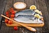 Raw sea bass on a wooden board — Stock Photo