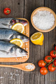 Fresh fish on chopping board with salt — Stock Photo