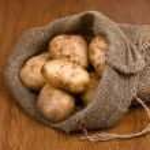 Harvest potatoes in burlap sack, sideways — Stock Photo #6672086
