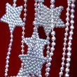 Silver Stars garland on red background — Stock Photo