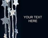 Silver Stars garland on dark background — Stock Photo