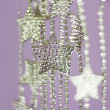 Silver Stars garland on purple background — Stock Photo