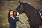 Young woman with a horse on nature — Stock Photo
