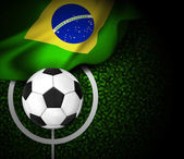 Football field with ball and flag of Brazil — Stockvektor