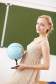 Teacher at school with a globe — Stock Photo