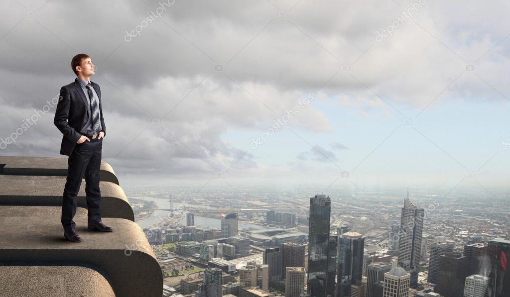 Business man standing high over a cityscape  — Stock Photo #12455707
