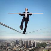 Balancing businessman and cityscape — Stock Photo
