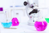 Chemistry laboratory glassware with colour liquids — Stock Photo