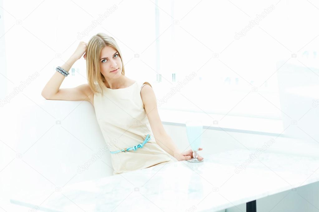 Portrait of a young blond woman sitting in cafe — Stock Photo #12559852