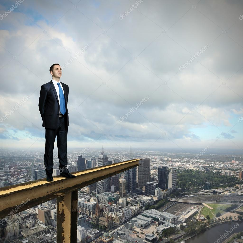 Business man standing high over a cityscape  — Stock Photo #12559927