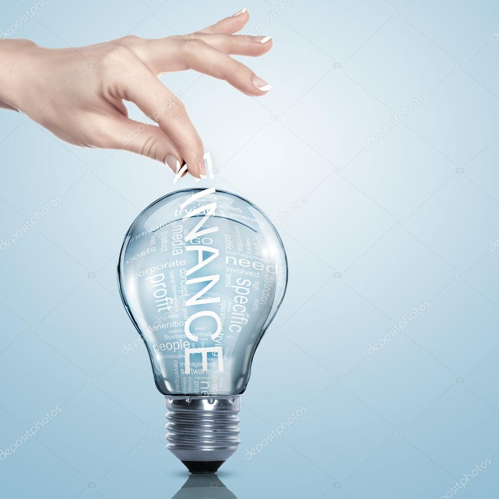 Hand putting a busines term into a light bulb — Stock Photo #12559986