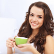 Young woman having cup of tea at home — Stock Photo #12673638
