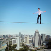 Balancing businessman and cityscape — Stock Photo