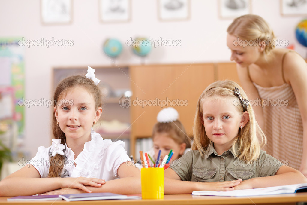 Young female teacher working with children at school — Stock Photo #12782863