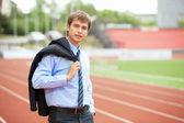 Affärsman på athletic stadium och travbana — Stockfoto