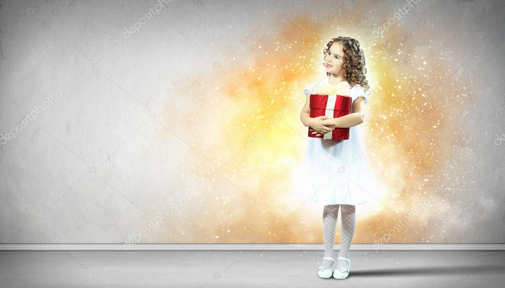 A cute young girl holding a christmas gift, dark background with christmas light bokeh  Stock Photo #13350510
