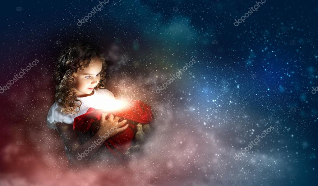 A cute young girl holding a christmas gift, dark background with christmas light bokeh — Stock Photo #13350638