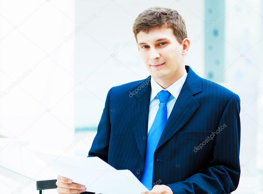 Young businessman in suit working in bright office, standing — Stock Photo #13383246