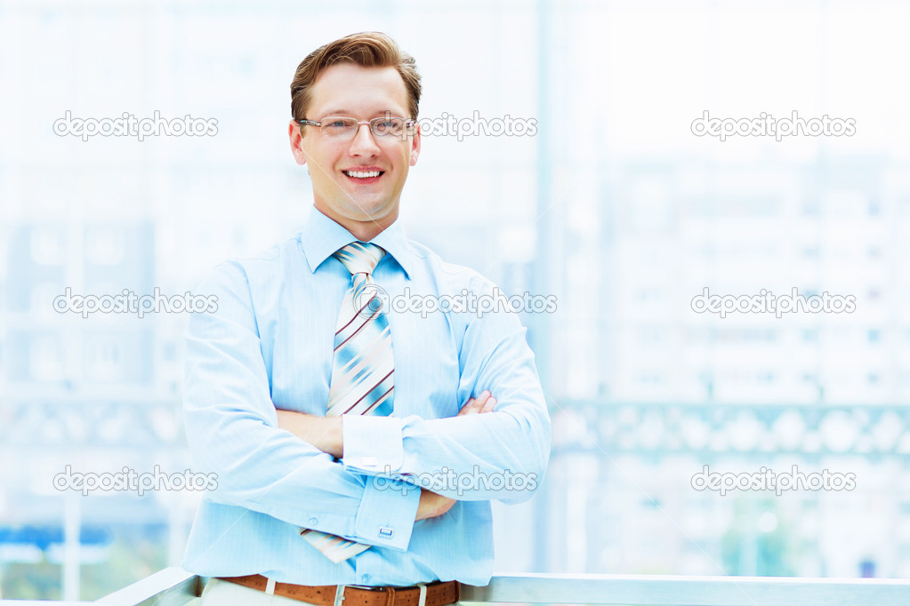 Young businessman in suit working in bright office, standing — Stock Photo #13383290