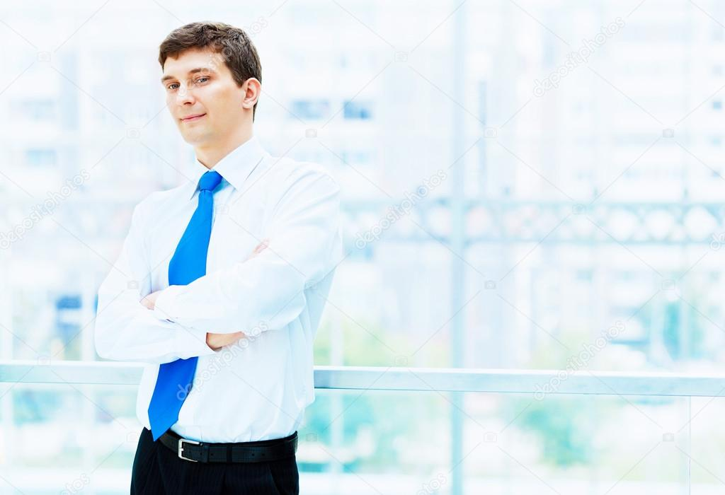 Young businessman in suit working in bright office, standing — Stock Photo #13383448