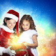 Little girl with christmas gifts and santa - Stock Photo