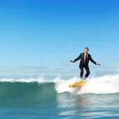 Businessman surfing on the waves of the ocean — Stock Photo