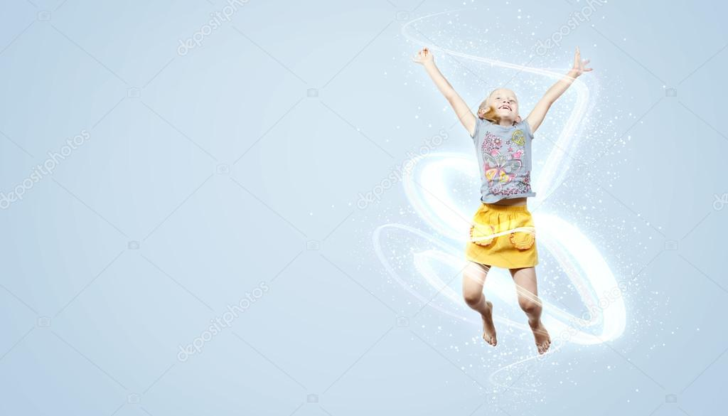 Photo of little girl jumping and raising hands against light background — Stock Photo #13512067