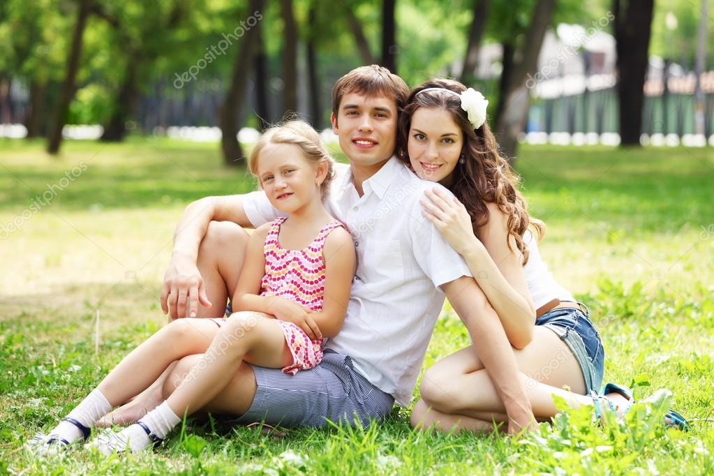 Young Family Outdoors on the grass in Park in summer — Stock Photo #13553937