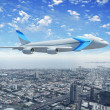 White passenger plane flying above a city - Stock Photo