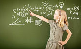 Scoolgirl staande in de buurt van blackboard — Stockfoto