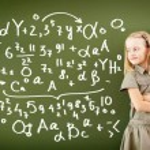 Scoolgirl standing near blackboard — Stock Photo