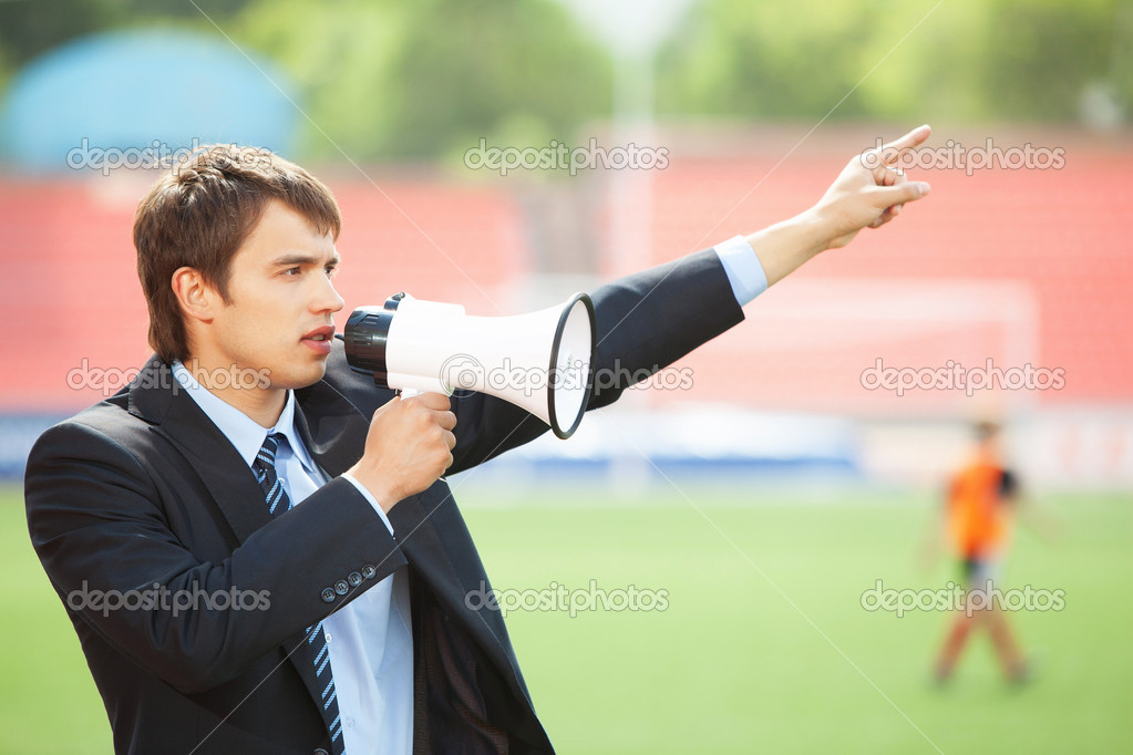 Businessman in black suit with loudspeaker at athletic stadium — Stock Photo #13921585