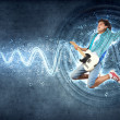 Stock Photo: Young mplaying on electro guitar and jumping