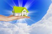 Huset i händerna på blå himmel — Stockfoto