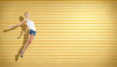 Pretty modern slim hip-hop style woman jumping dancing on a colour background — Stock Photo