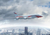 White passenger plane flying above a city — Stock Photo