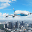 White passenger plane flying above a city — Stock Photo #14697123