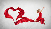 Dancing young woman with flying fabric — Stock Photo
